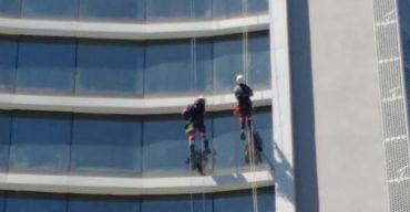 dois homens fazendo instalação de pele de vidro na fachada de prédio