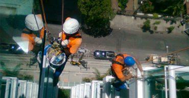 Dois profissionais realizando serviços em altura em um prédio usando cinto para alpinismo industrial
