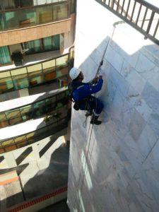 Profissional realizando seu trabalho em um prédio, utilizando cinto para alpinismo industrial