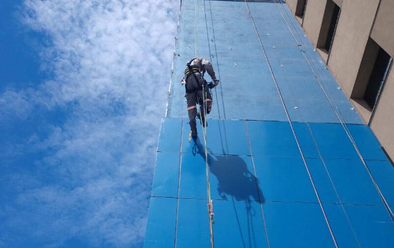 As cores para fachada comercial são importantes para que o edifício se diferencie dos outros. Na imagem, pode-se ver nosso funcionário em um prédio de cor azul.