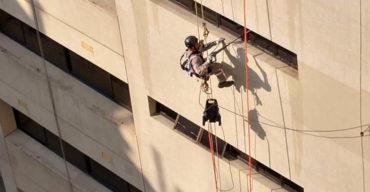 Trabalhador em altura executando o que é ACM em uma fachada
