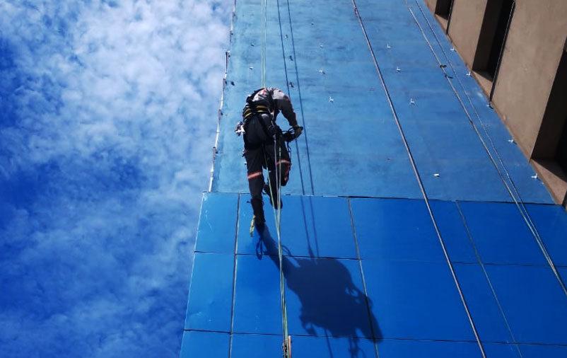Trabalhador fazendo serviço em altura para melhorar a estrutura da empresa