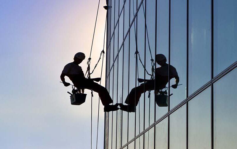 Alpinista industrial realizando um serviço no edifício