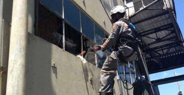 homem trabalhando em modernização de fachada em altura