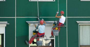 dois trabalhadores em uma corda de segurança realizando o serviço de pintura em fachadas