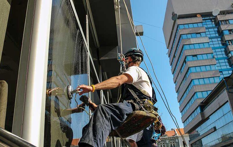 Na imagem vemos um alpinista industrial fazendo tratamento de superfícies em fachadas.