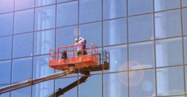 Profissional trabalha em altura para remover manchas na fachada de vidro