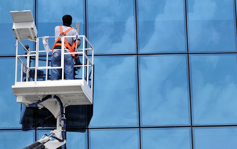 Vemos um profissional realizando a reforma de fachada predial.